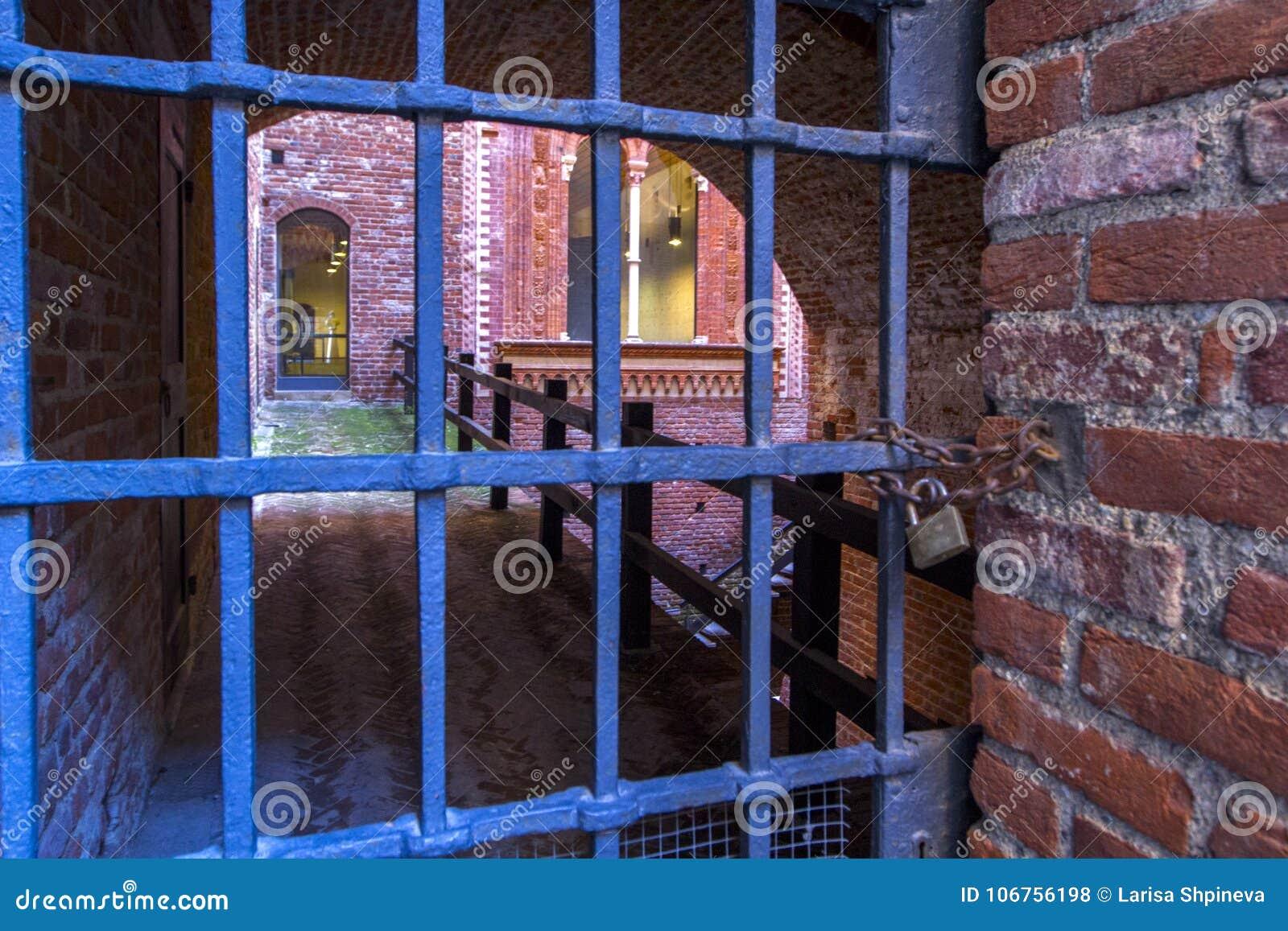 Puerta vieja en la fortaleza, vieja abertura de la mazmorra de la rejilla del hierro Diseño arquitectónico de piedras y de ladril