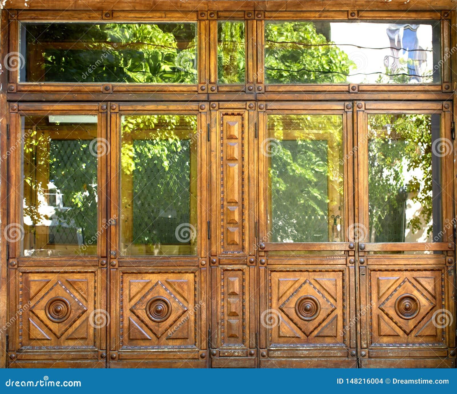 Puertas de madera delanteras viejas con las ventanas y con los modelos