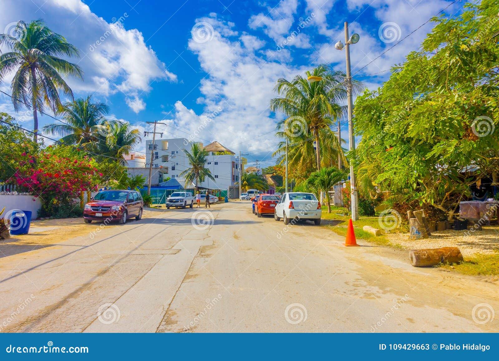 Puerto Morelos Meksyk, Styczeń, - 10, 2018: Plenerowy widok niektóre domy z wiele samochodami parkującymi w ulicie Puerto