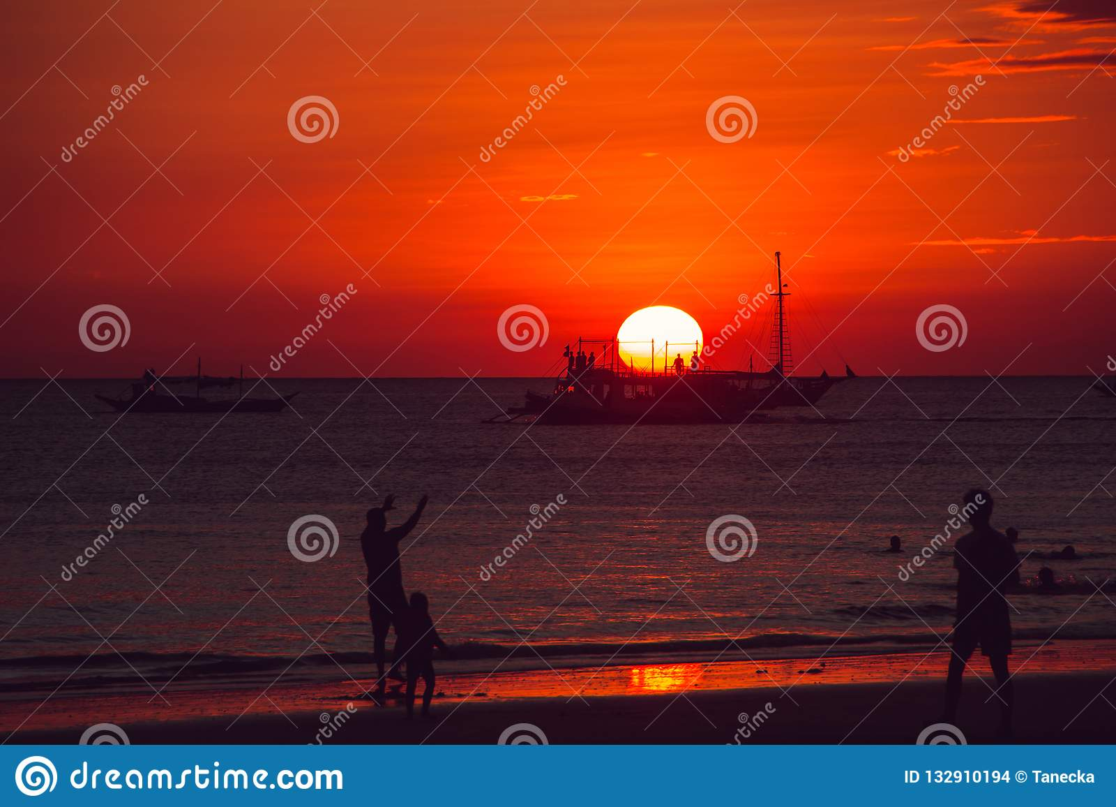 Puesta del sol anaranjada dramática del mar con las siluetas del velero y de la gente Adultos jovenes Viaje a Filipinas Vacacione