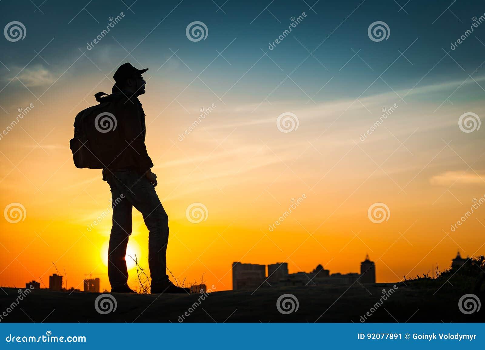 Puesta del sol asombrosa de observación de la silueta del viajero