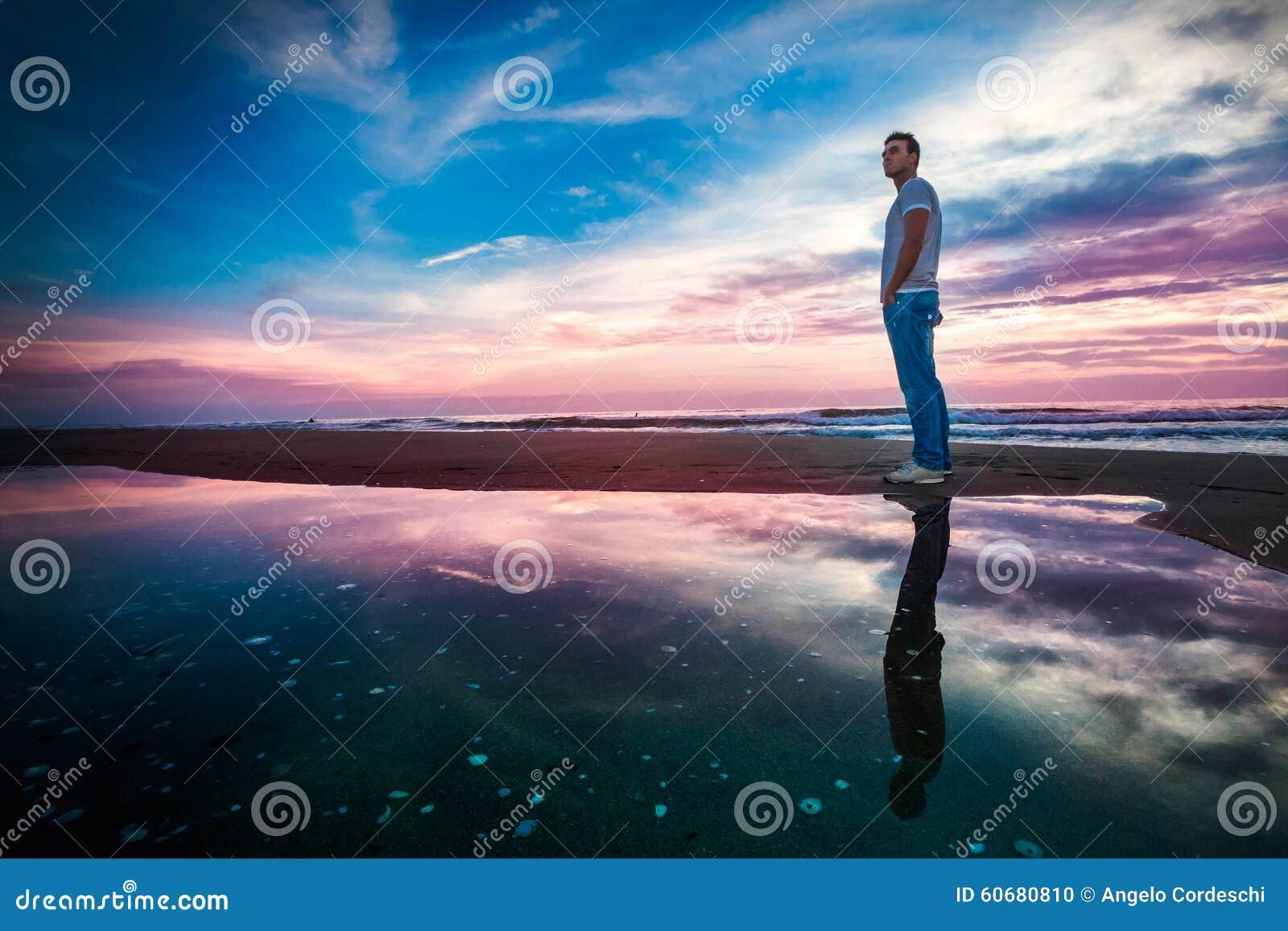 Puesta del sol asombrosa del mar con la reflexión Hombre solitario
