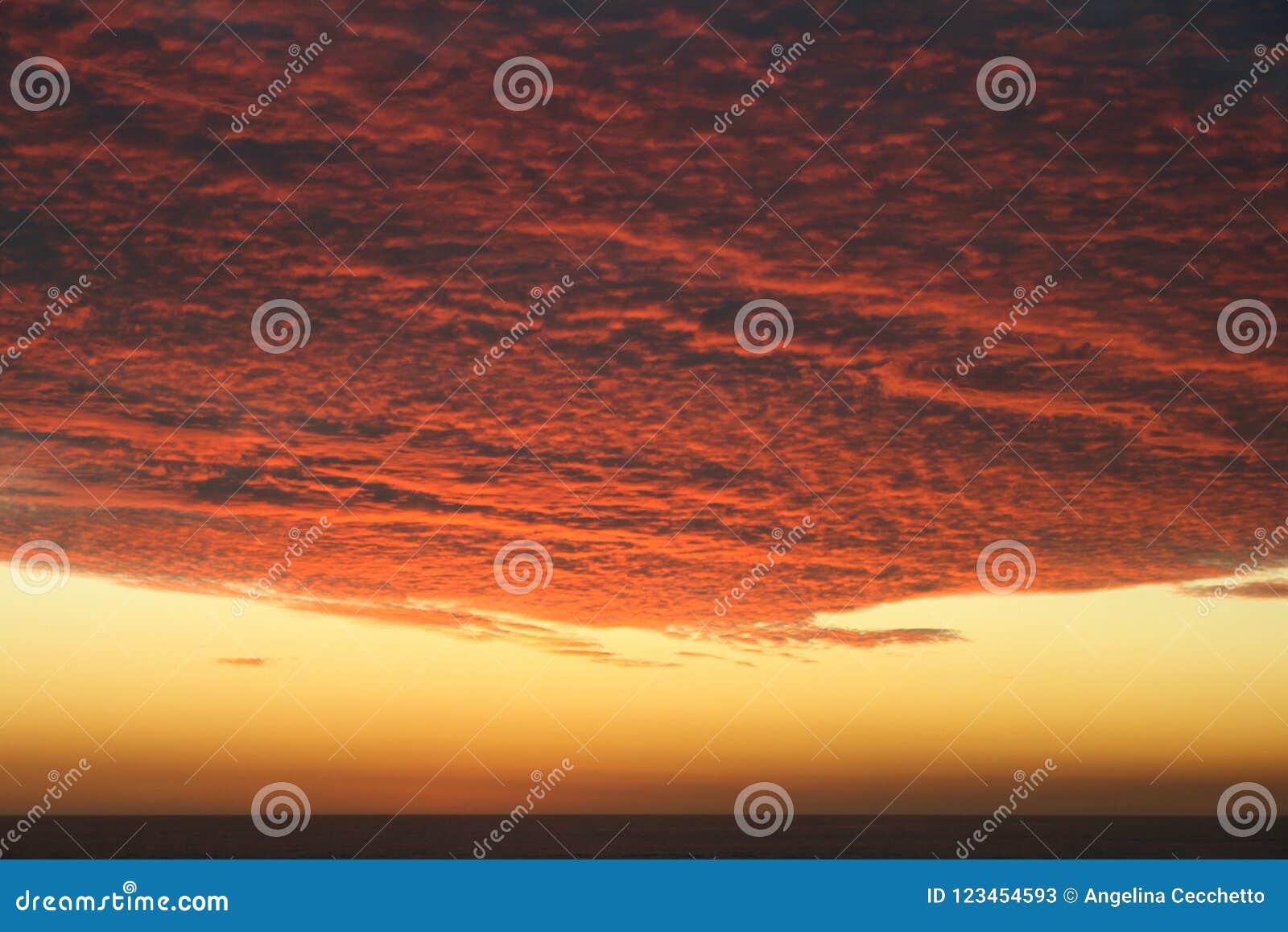 Puesta del sol carmesí volcánica dramática sobre el Océano Pacífico