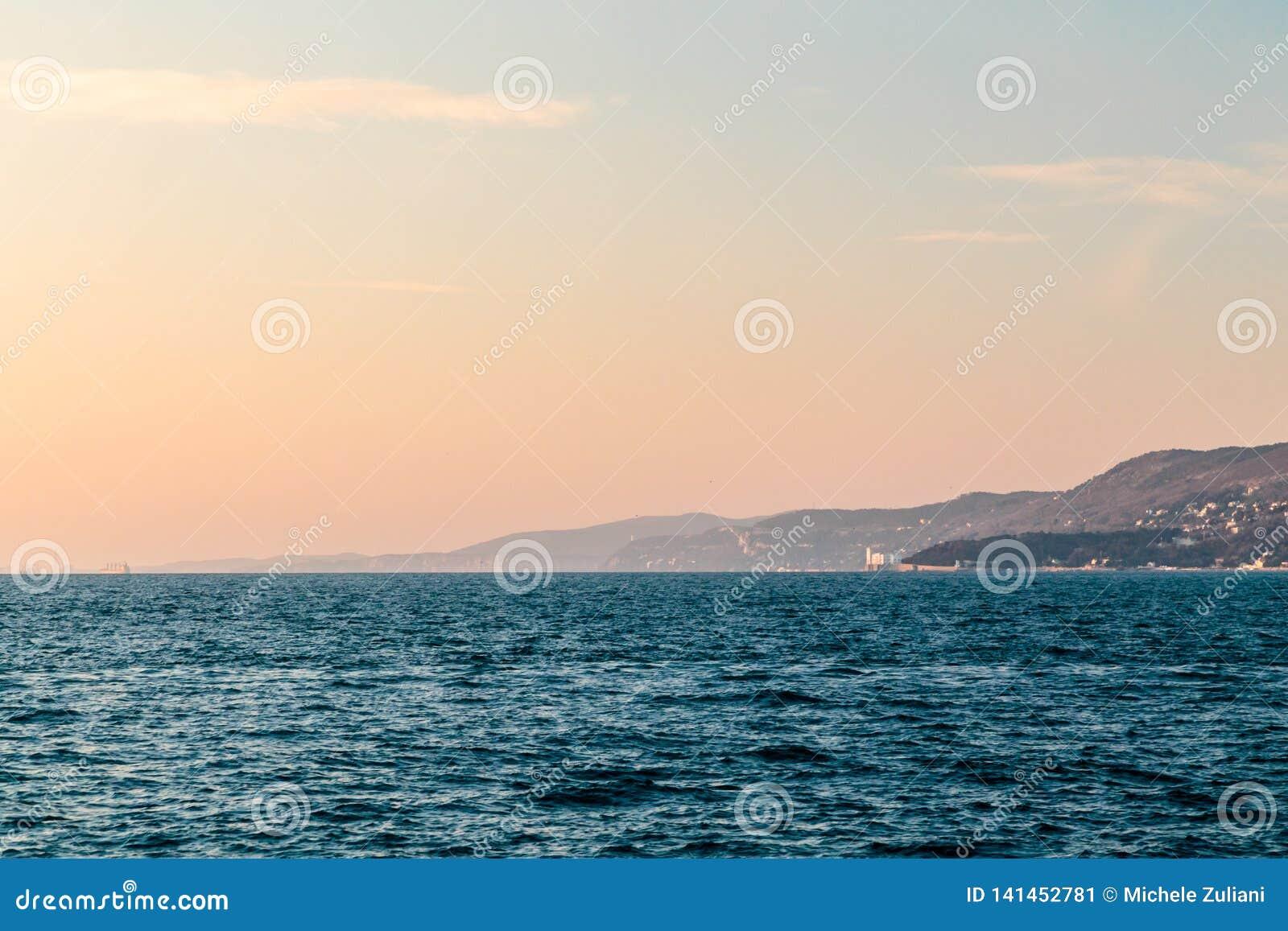 Puesta del sol colorida delante de la ciudad de Trieste