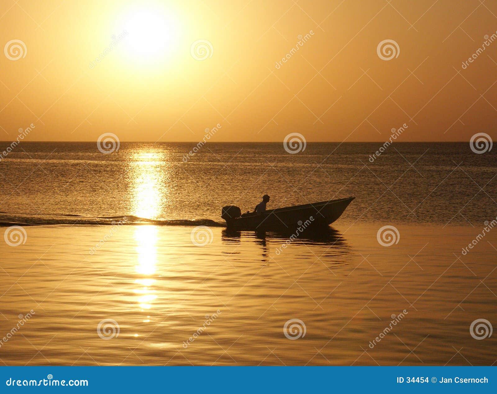 Puesta del sol con el hombre en barco