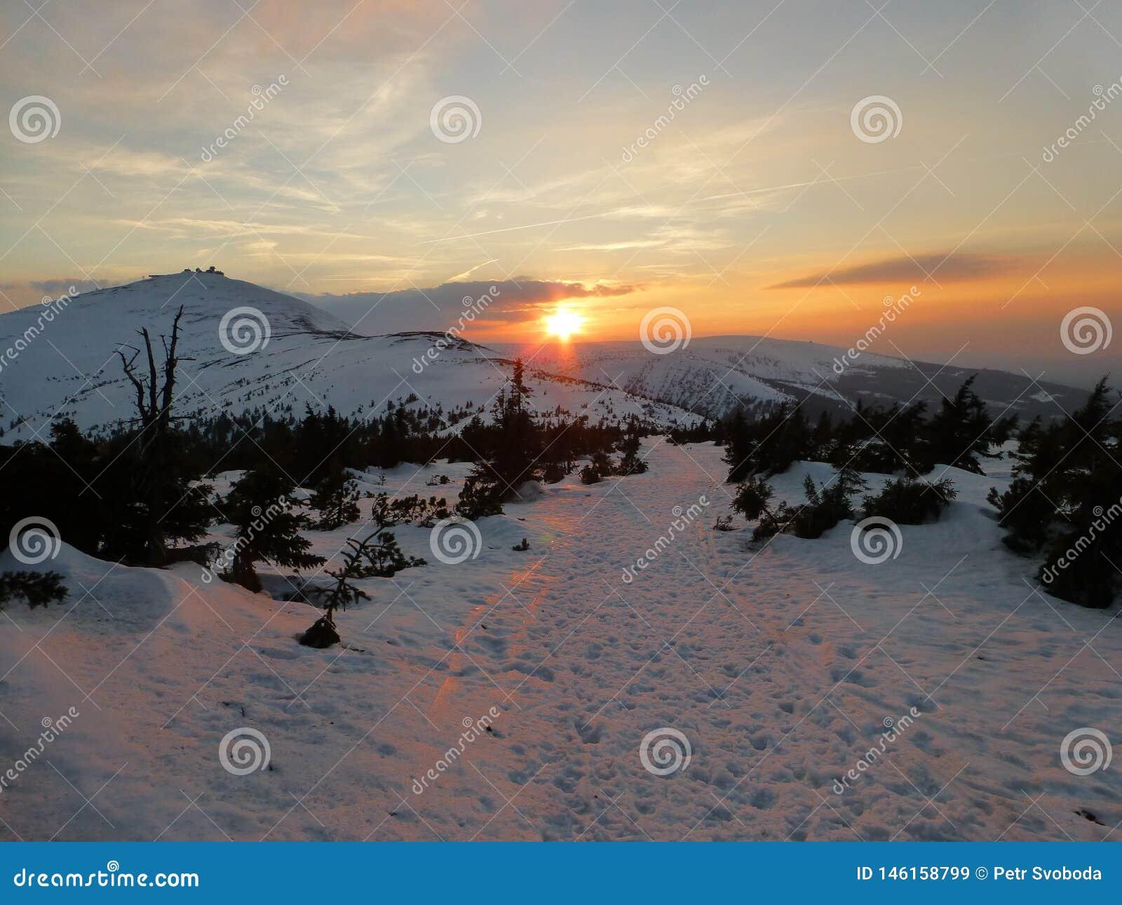 Puesta del sol con Snezka en las montañas gigantes en invierno