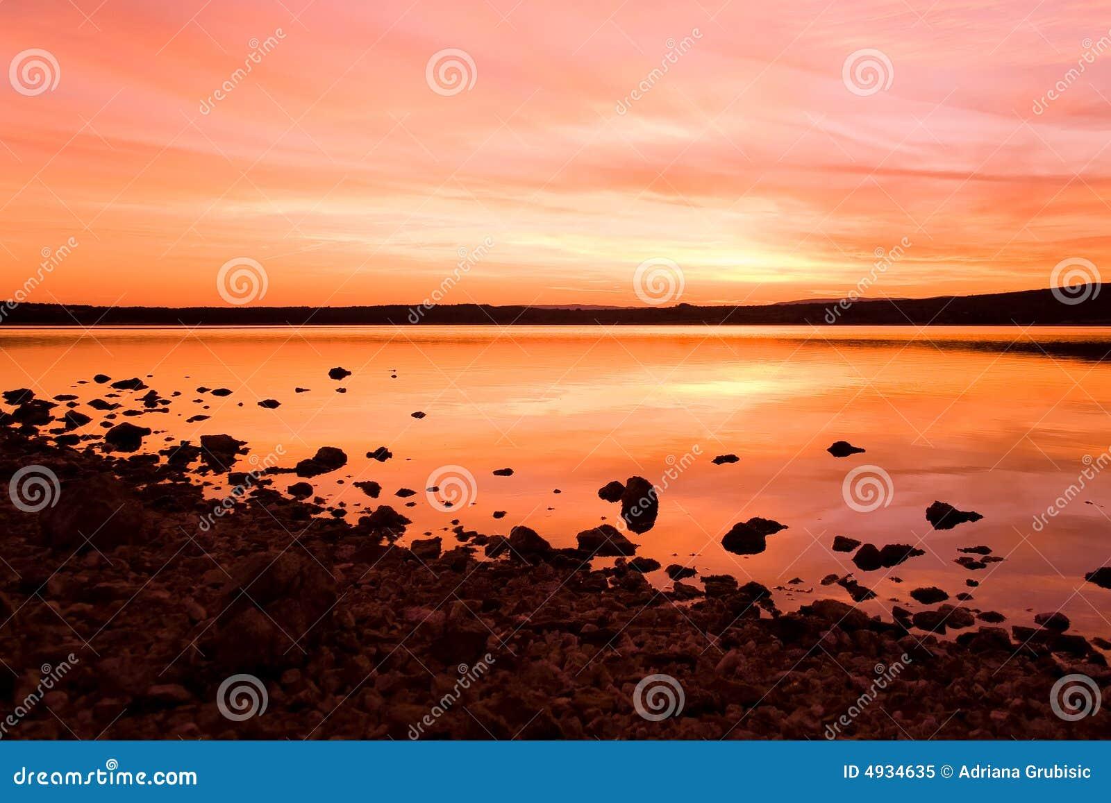 Puesta del sol de Idilic sobre la agua de mar