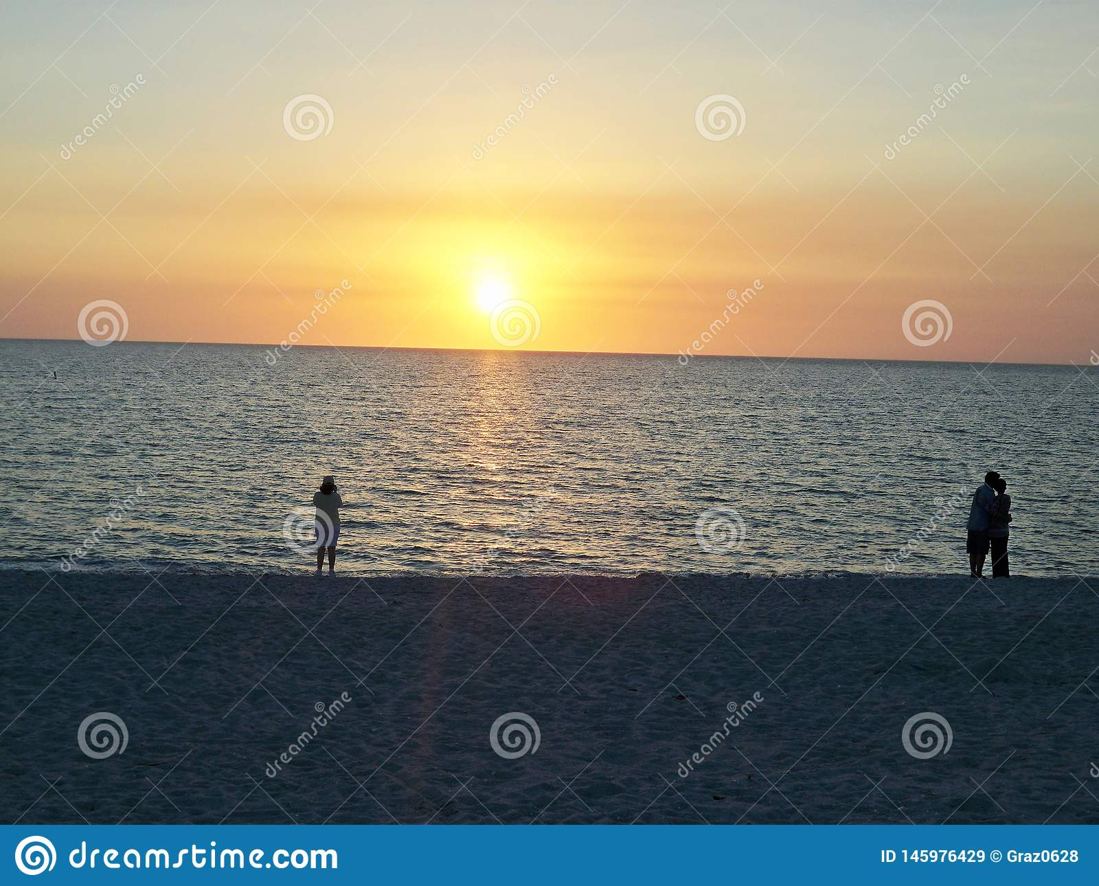 Puesta del sol de observaci?n de la gente en la playa