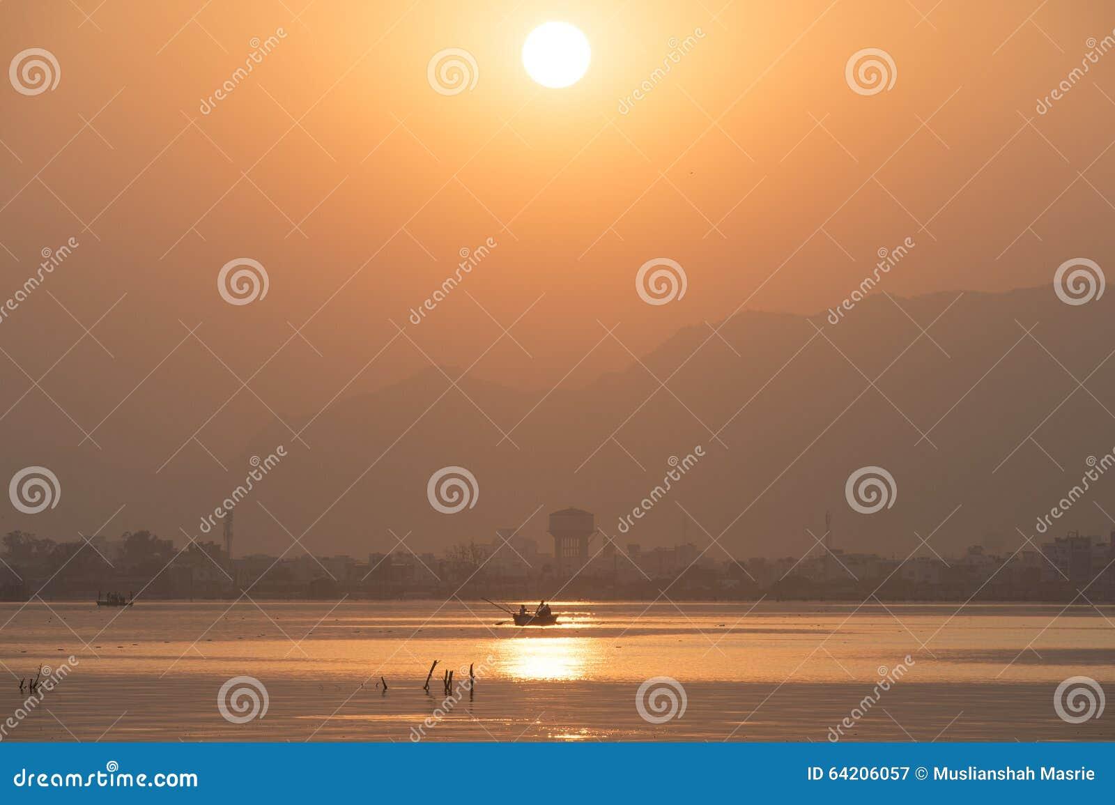 Puesta del sol de oro en el lago ana Sagar en Ajmer, la India con las siluetas