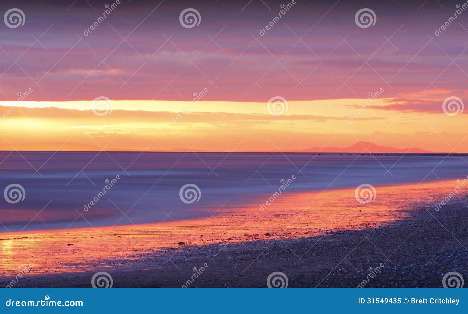 Puesta del sol de oro en la playa