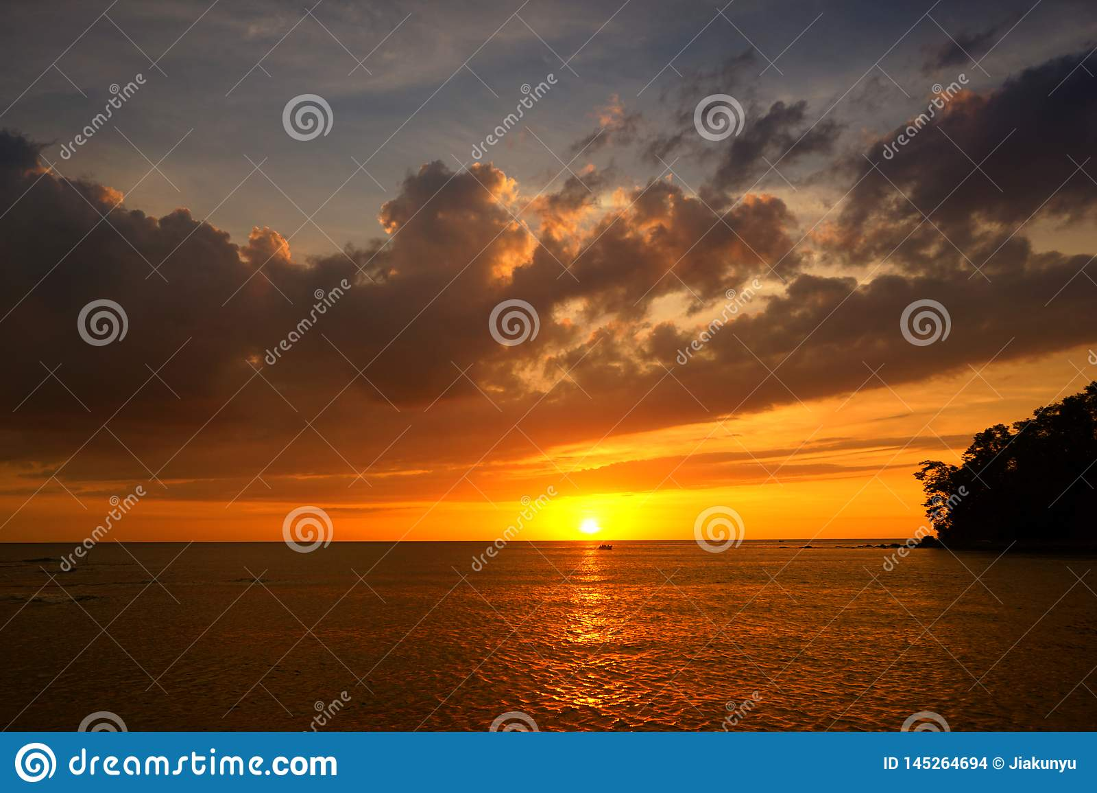 Puesta del sol de oro en la playa con resplandor de tarde La luz roja de la reflexión del mar como salida del sol