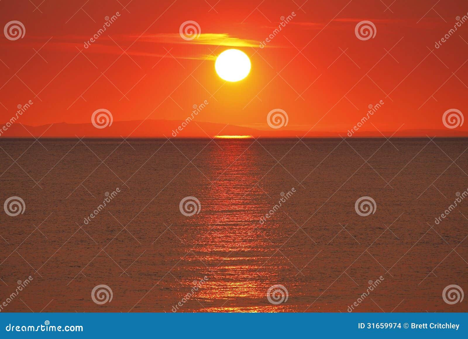 Puesta del sol de oro sobre el agua