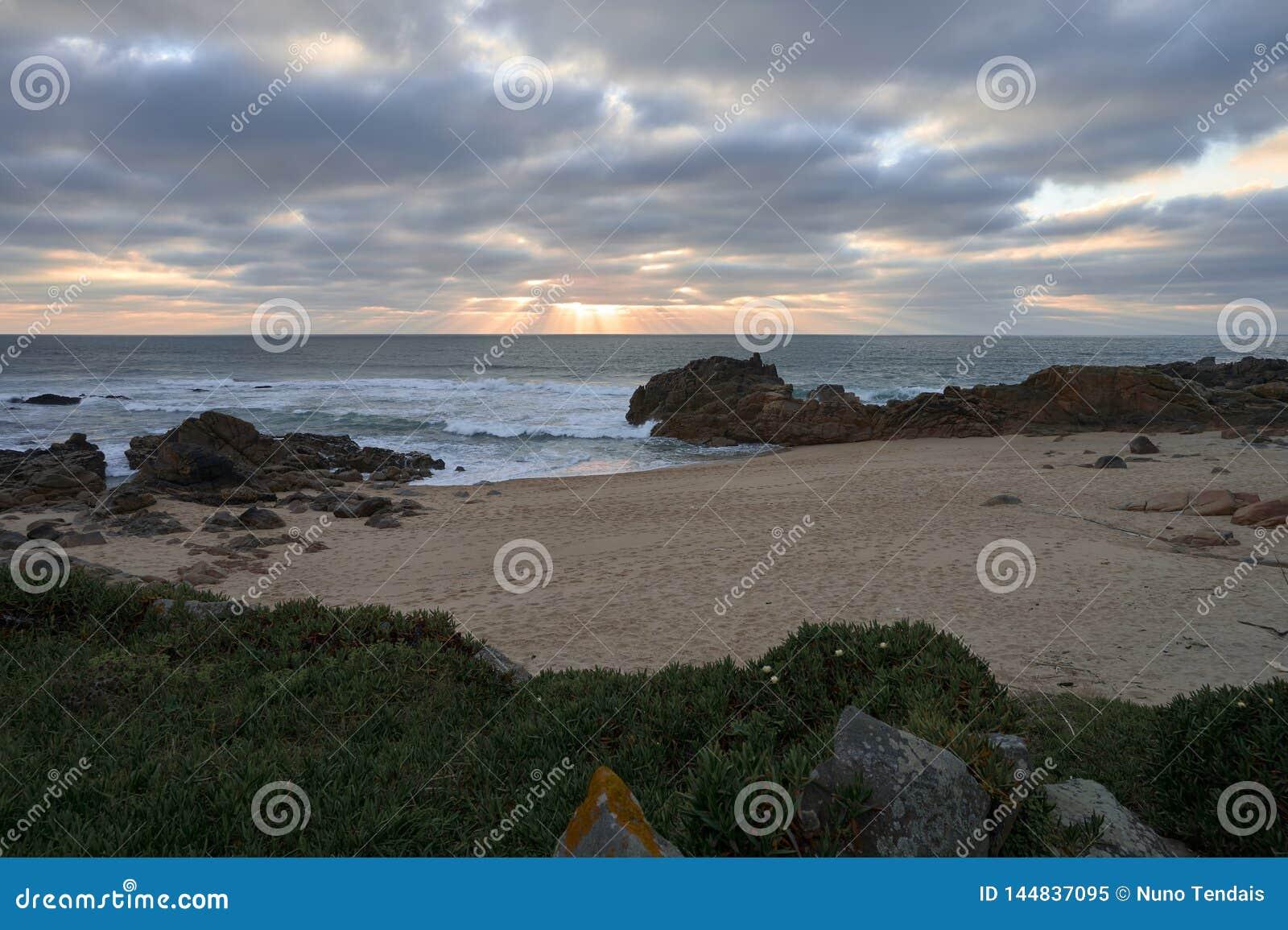 Puesta del sol debajo de las nubes oscuras en una playa rocosa