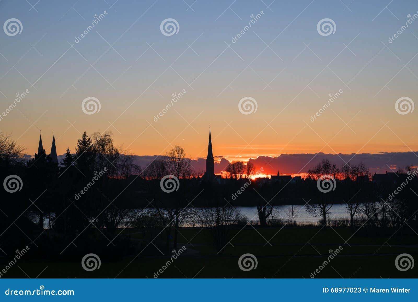 Puesta del sol detrás de las torres de iglesia de Luebeck, Alemania septentrional, PA