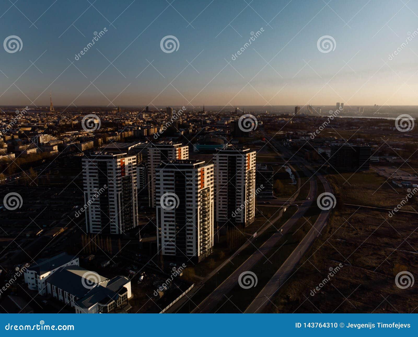 Puesta del sol dramática aérea del paisaje con una visión sobre rascacielos en Riga, Letonia - el centro de la ciudad viejo de la