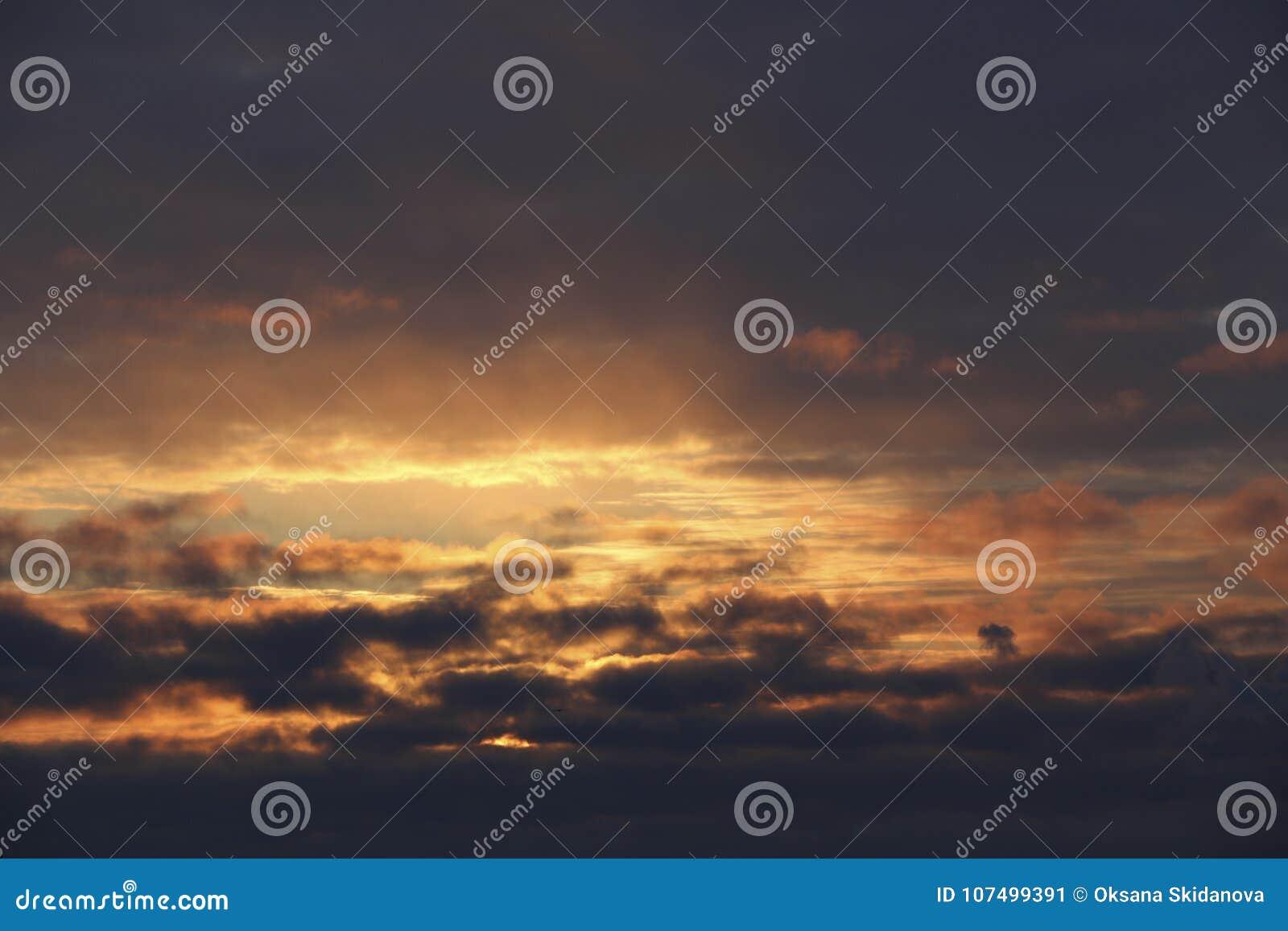 Puesta del sol el cielo del invierno de la tarde en nubes oscuras densas el sol brilla la luz caliente amarilla brillante a travé
