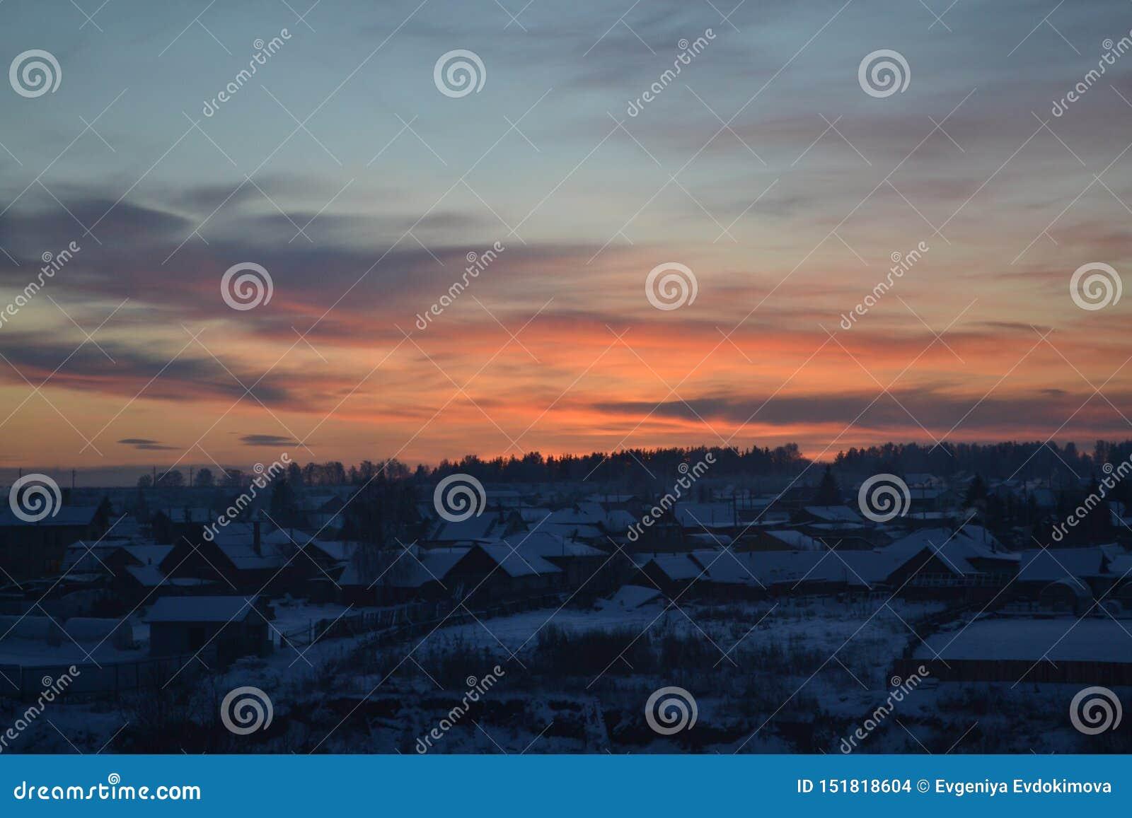 Puesta del sol en el cielo sobre el pueblo ruso del invierno