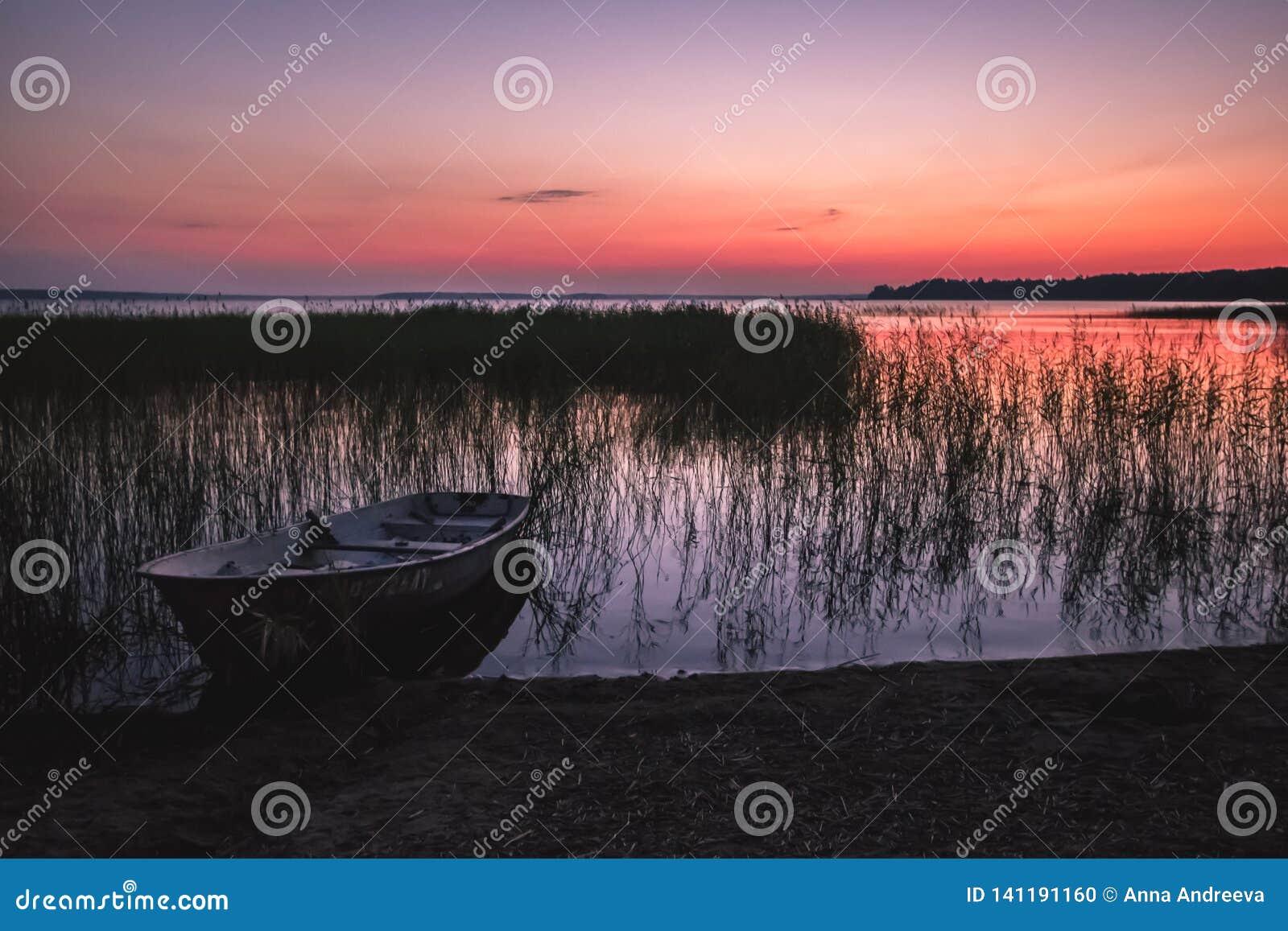 Puesta del sol en el lago, barco de pesca en la orilla