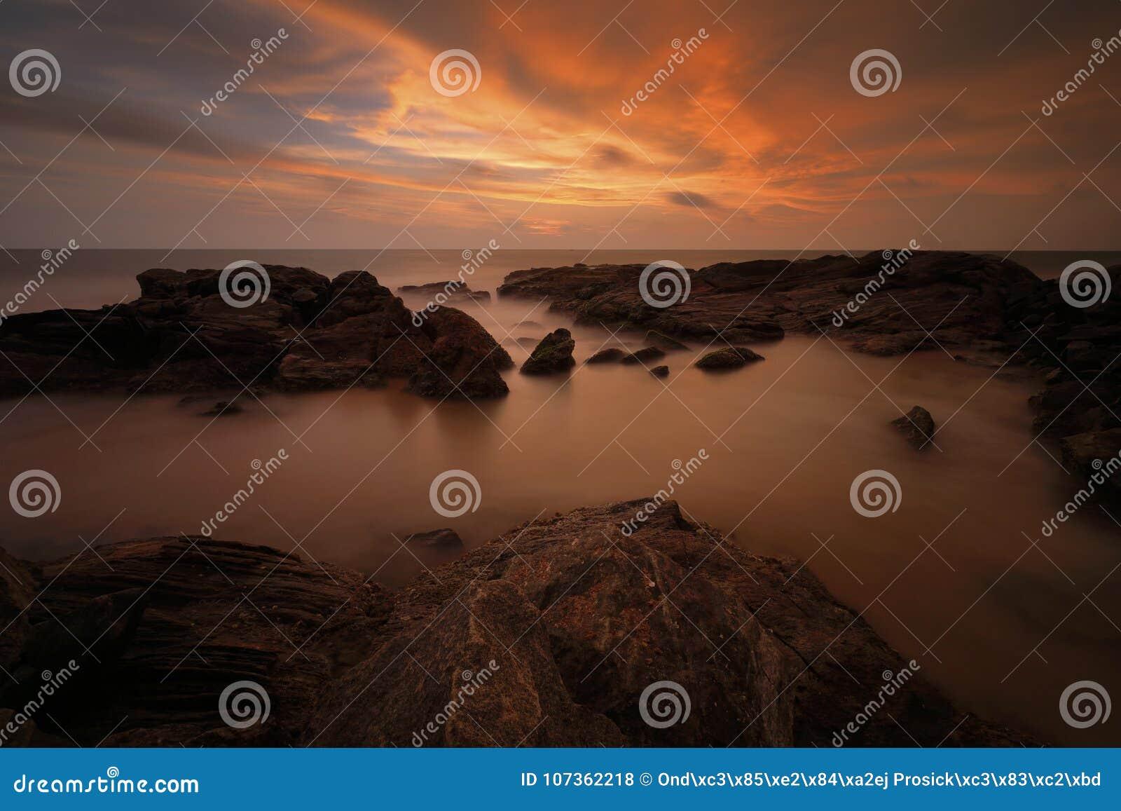 Puesta del sol en el mar de la costa con el sol Costa de la roca con el sol durante puesta del sol Puesta del sol en Bentota, Sri