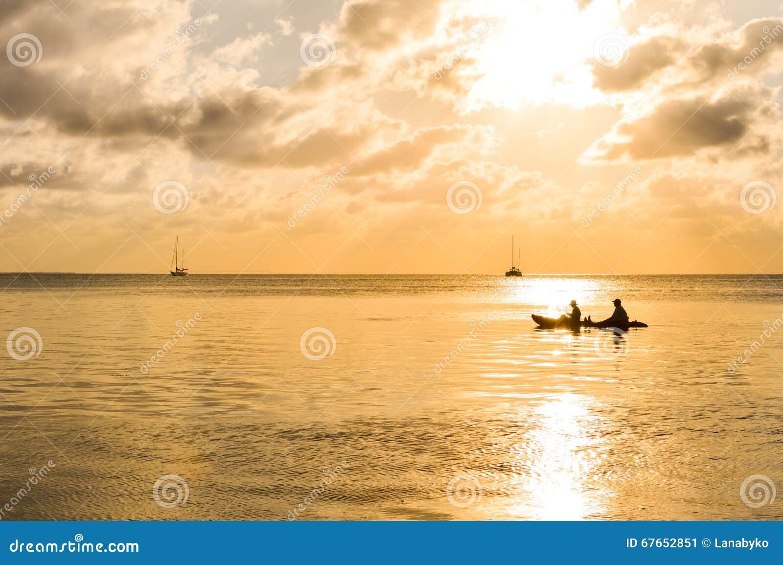 Puesta del sol en el mar del Caribe por la isla del calafate de Caye, Belice