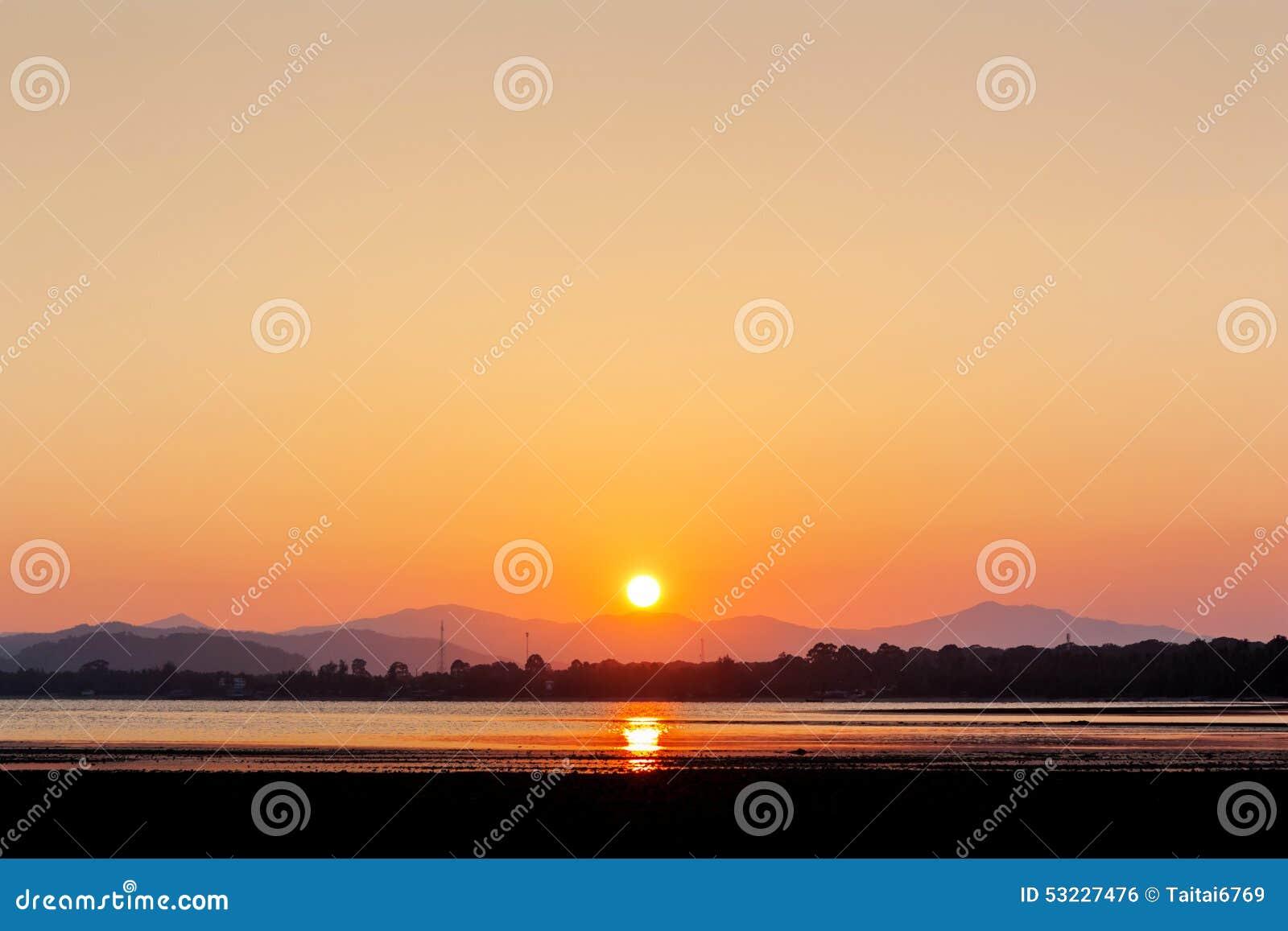 Puesta del sol en el tiempo del crepúsculo de la playa
