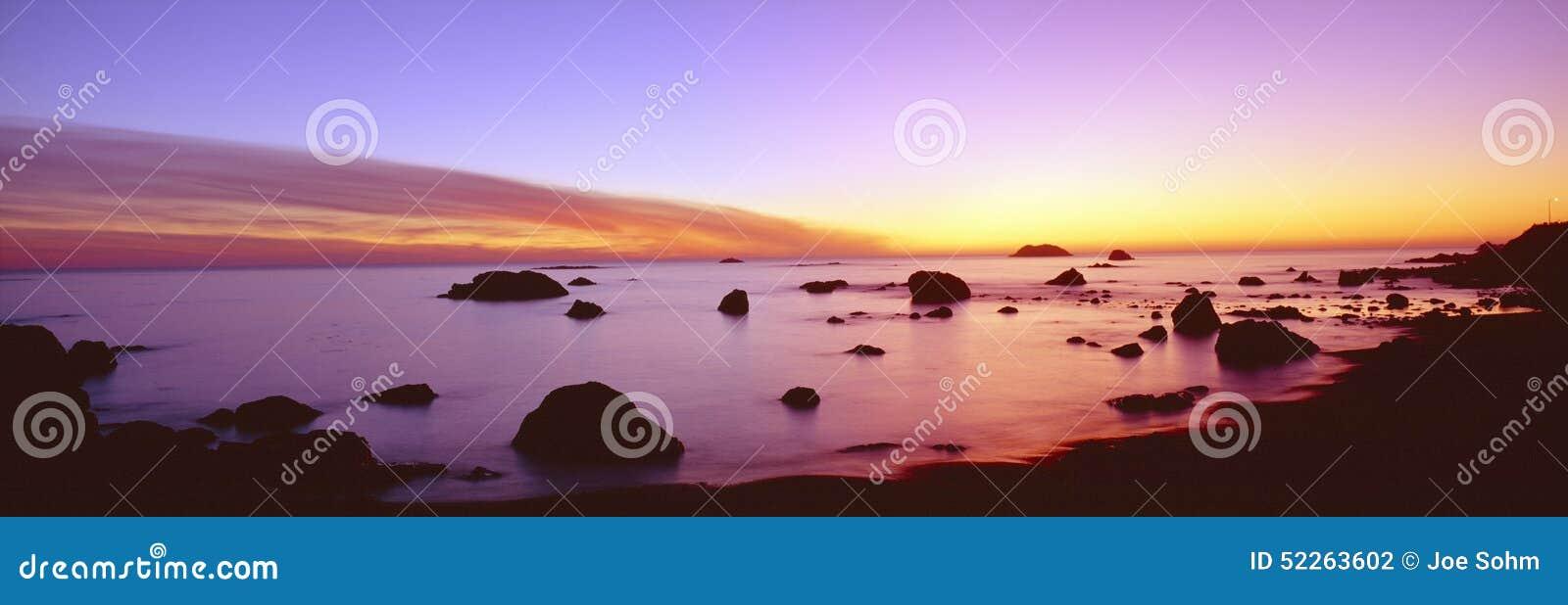 Puesta del sol en la línea de la playa pacífica rocosa, California septentrional
