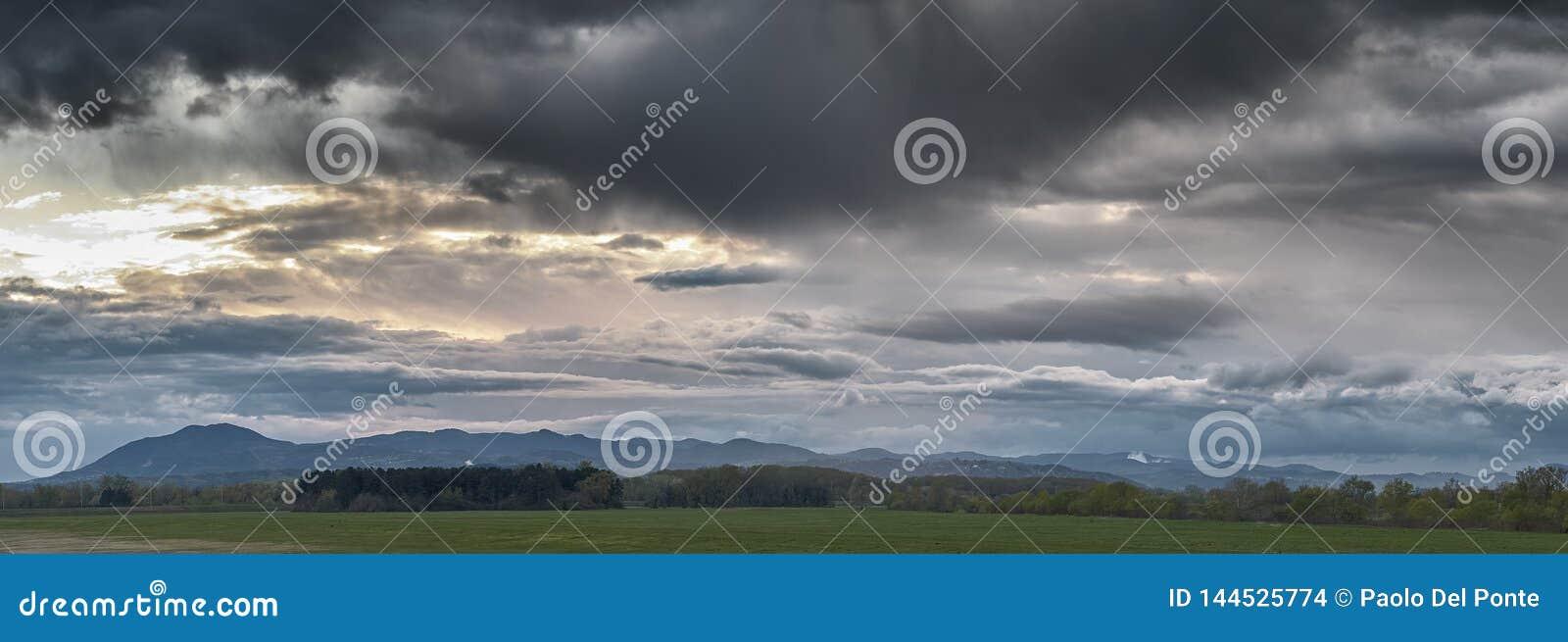 Puesta del sol en un cielo dramático de las nubes sobre un prado y un pequeño bosque del pino con las colinas en fondo, cerca de
