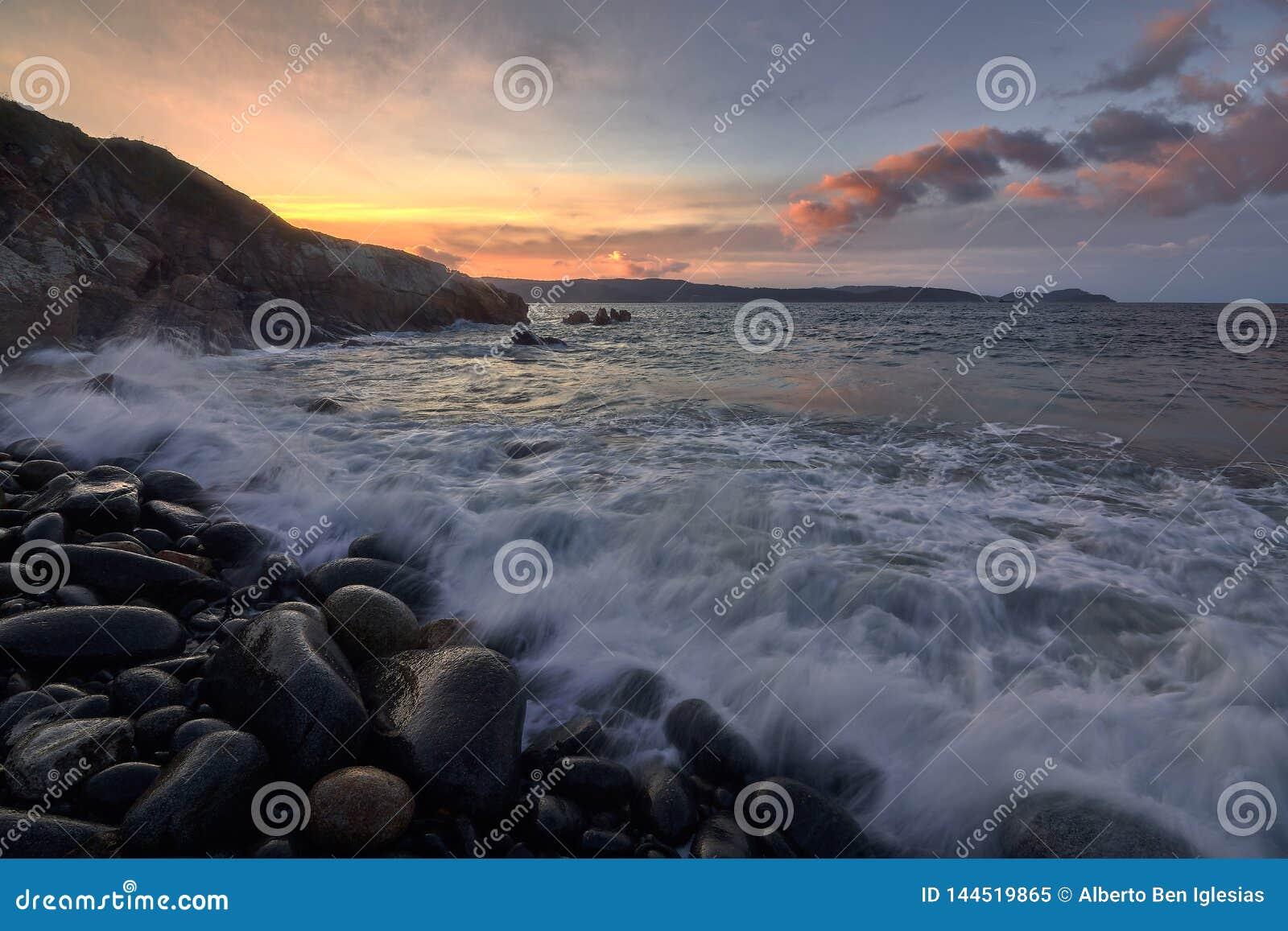 Puesta del sol en una playa de la roca