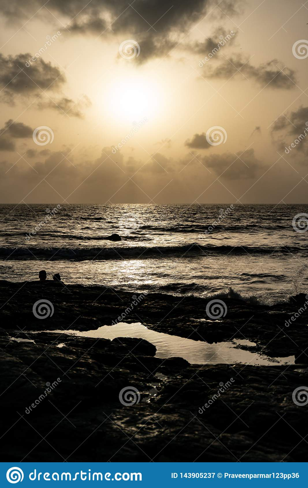 Puesta del sol en una playa rocosa