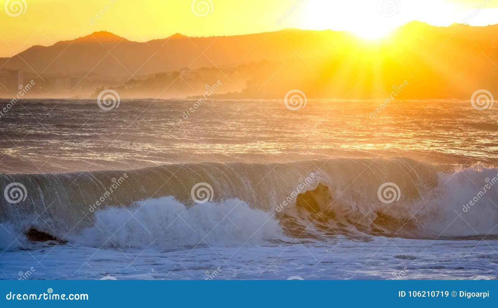 Puesta del sol hermosa en España con las ondas grandes, Costa Brava