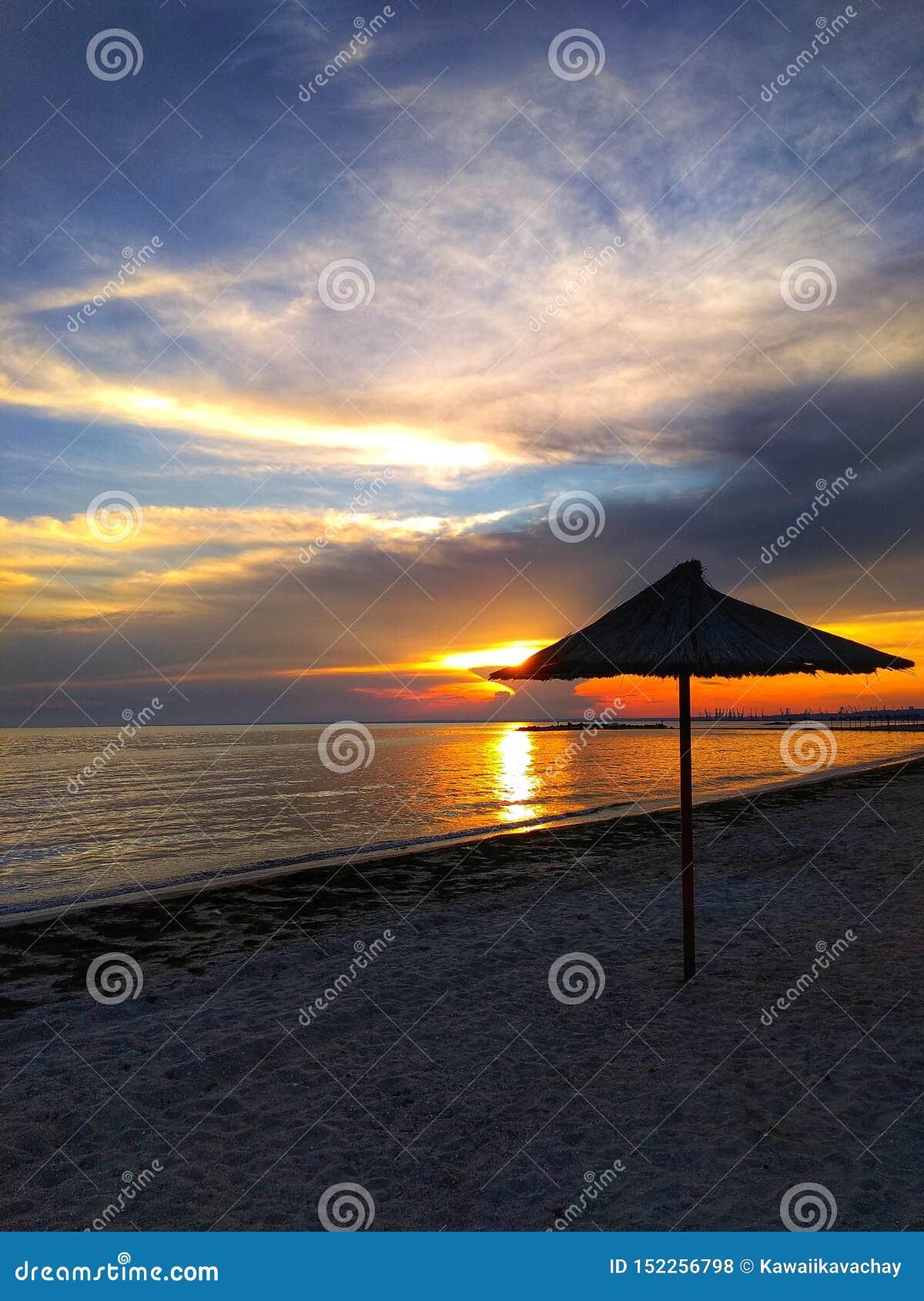 Puesta del sol hermosa en la playa arenosa Paraguas por el mar, calma, fondo natural hermoso de la paja