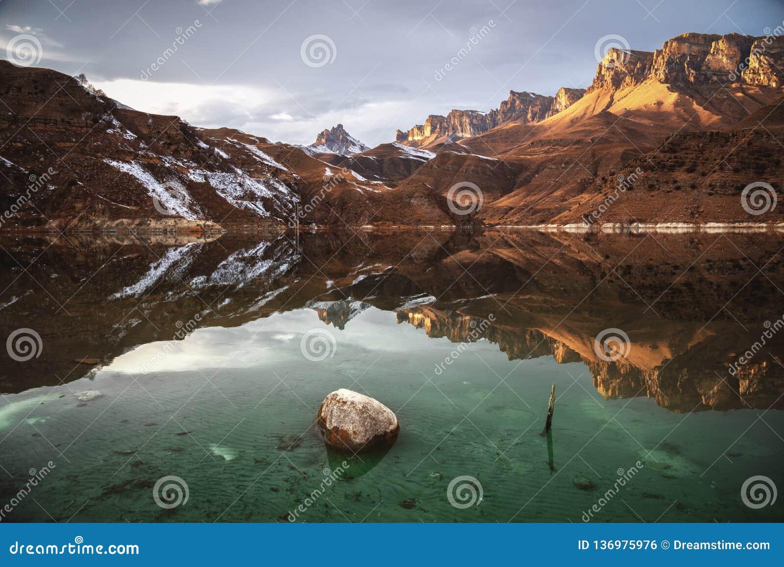 Puesta del sol hermosa en la reflexión de un lago de la montaña