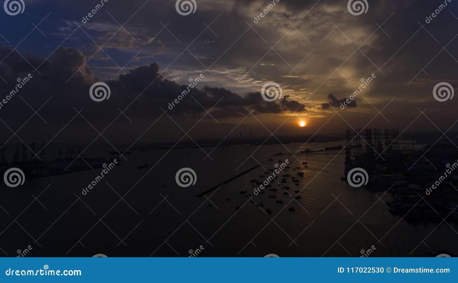 Puesta del sol hermosa, imponente sobre el agua, sobre los barcos en un muelle o un puerto de mirada industrial