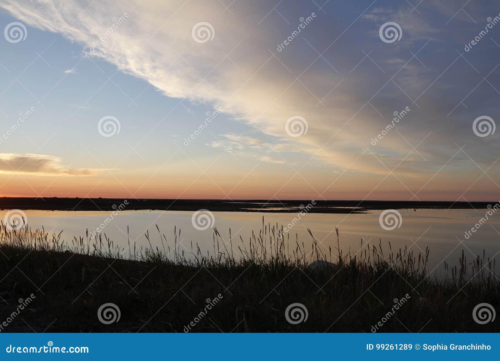 Puesta del sol hermosa sobre un paisaje ártico con las nubes en el cielo