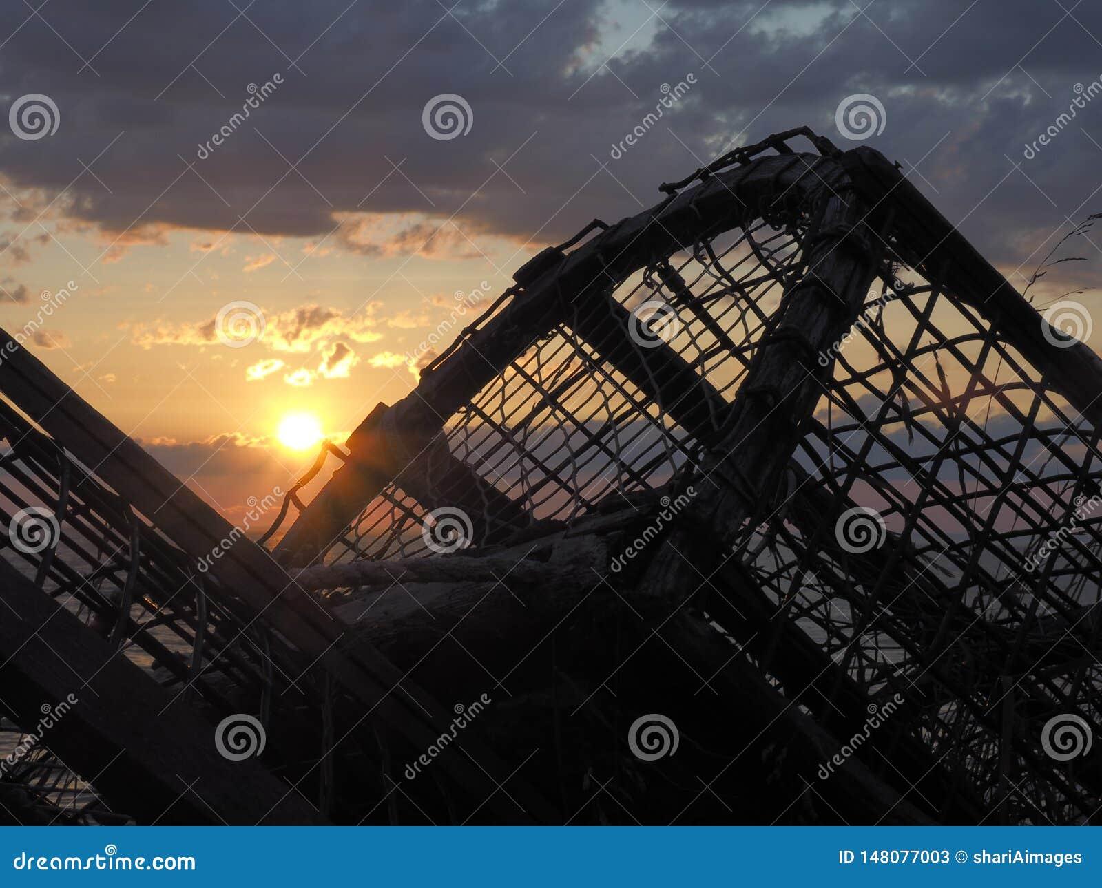 Puesta del sol nublada con las trampas de la langosta en silueta