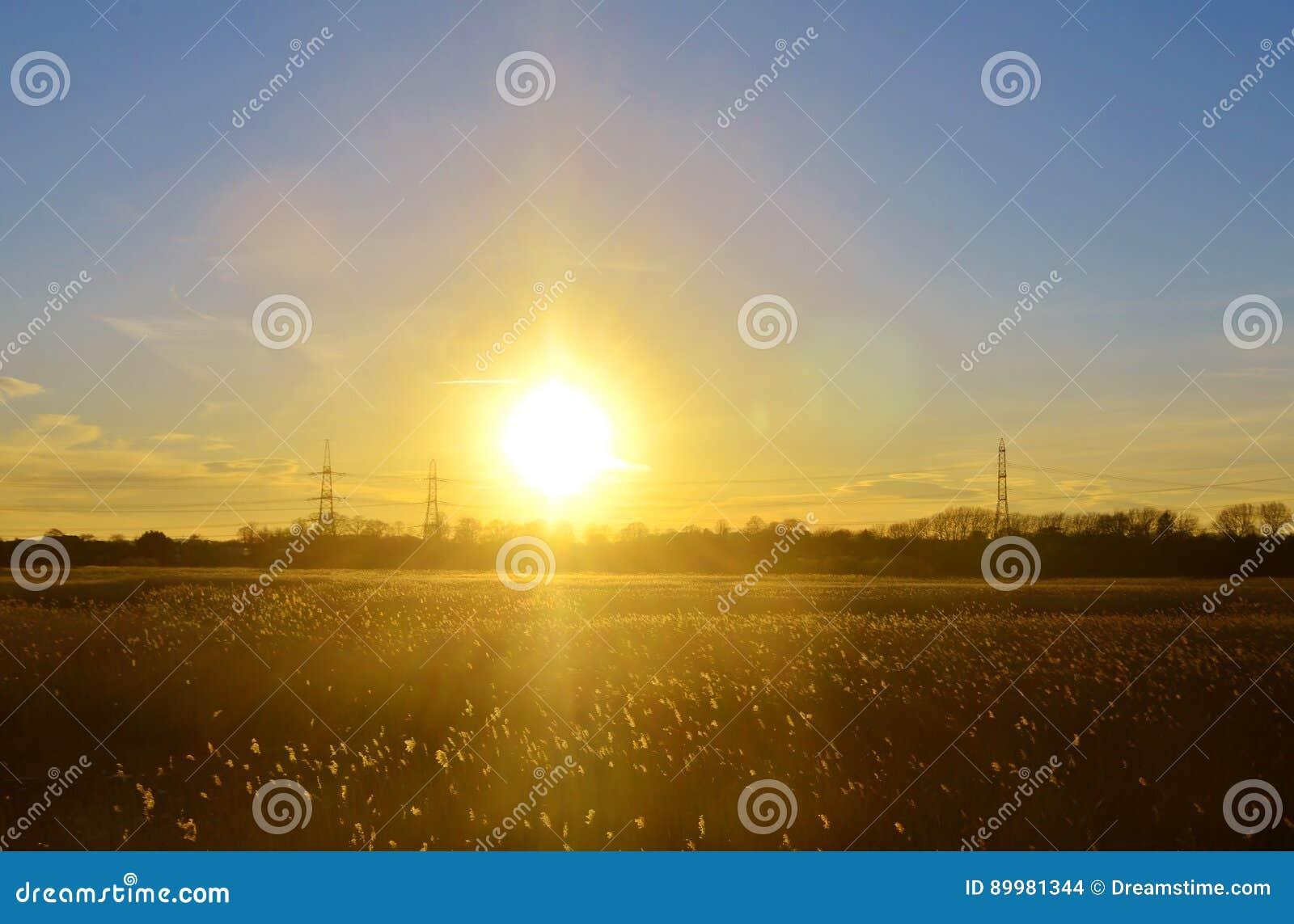 Puesta del sol sobre campo cerca del baño