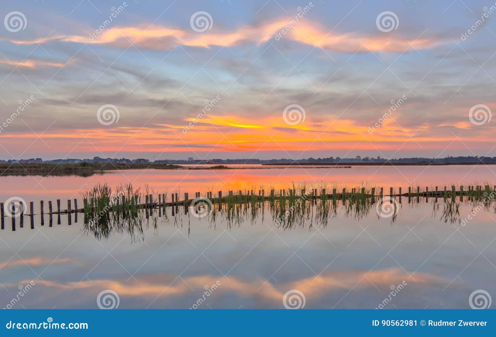Puesta del sol sobre el lago con el riverbank campshedding