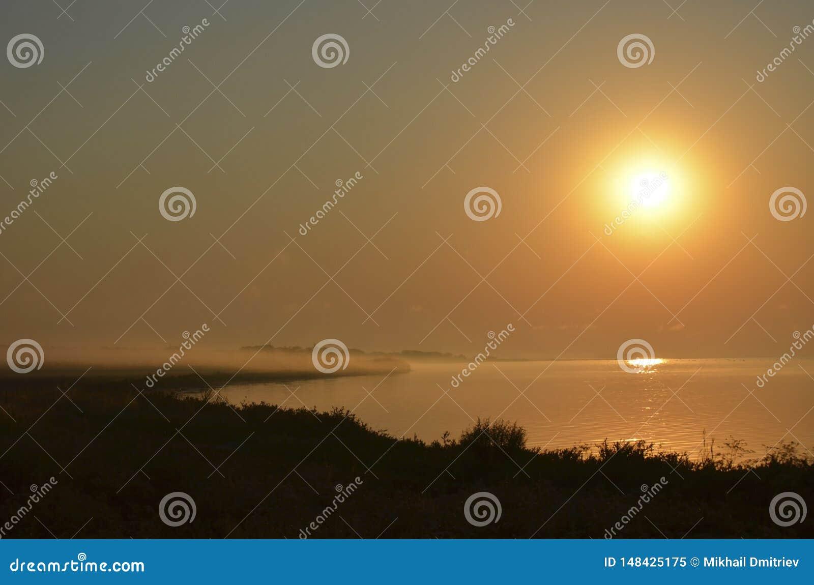 Puesta del sol sobre el mar neblina de la niebla