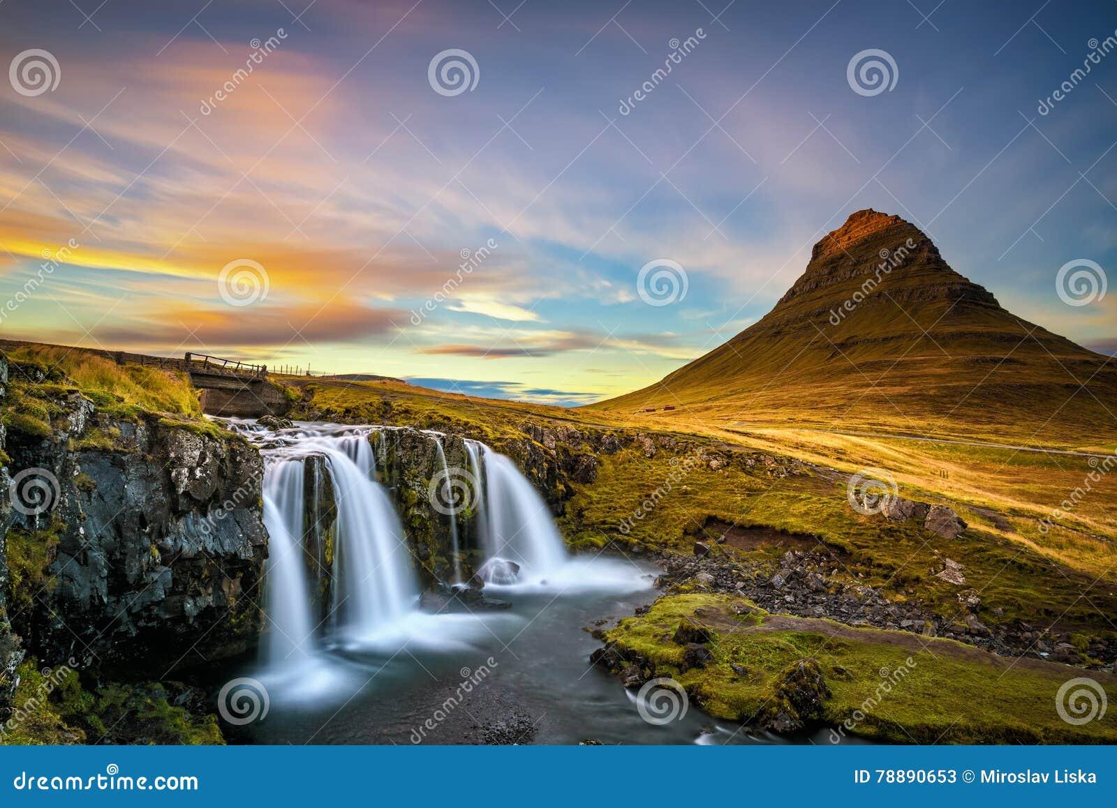 Puesta del sol sobre la montaña de la cascada y de Kirkjufell de Kirkjufellsfoss en Islandia