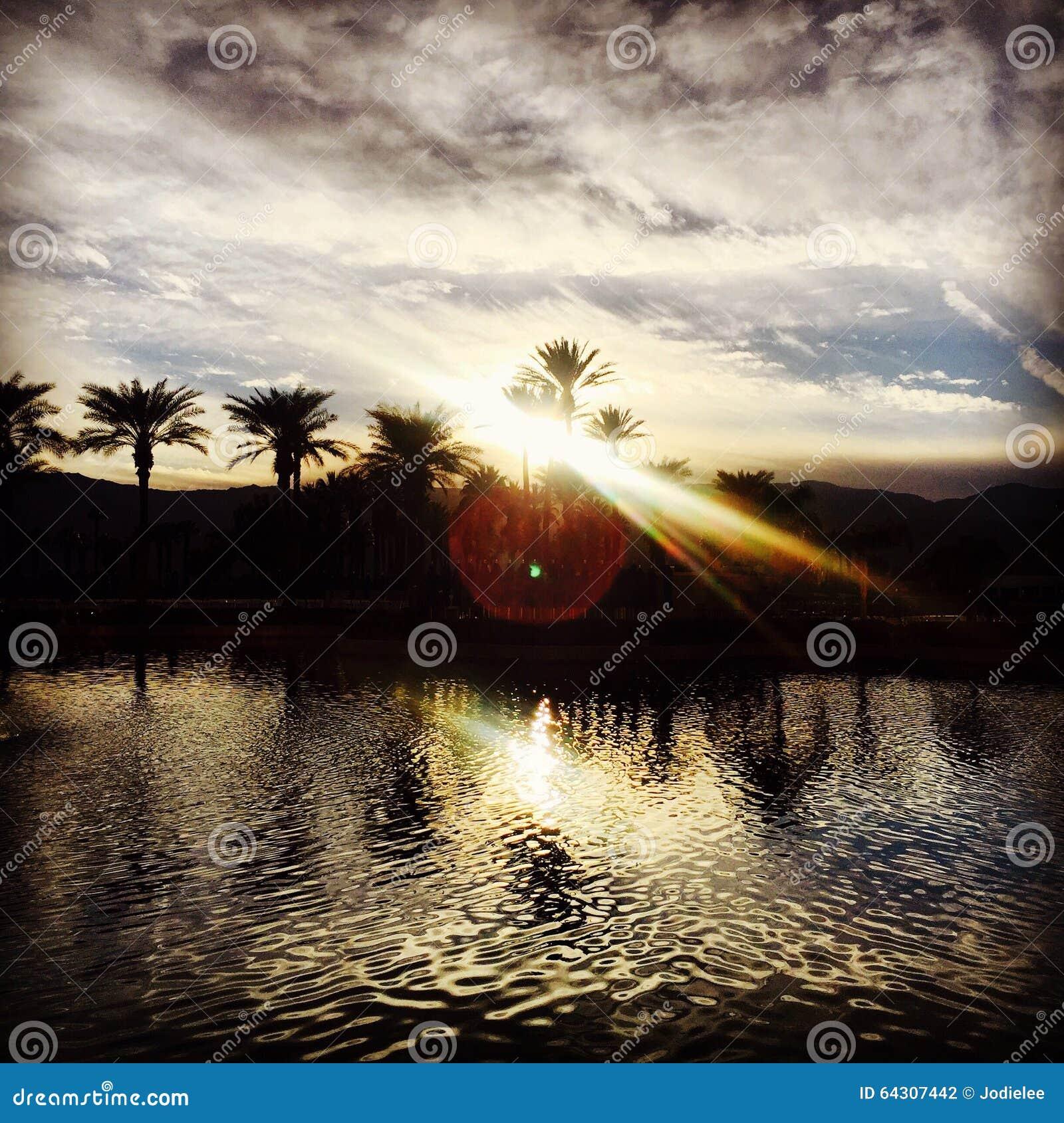 Puesta del sol sobre las montañas del desierto con agua en Palm Desert California los E.E.U.U.