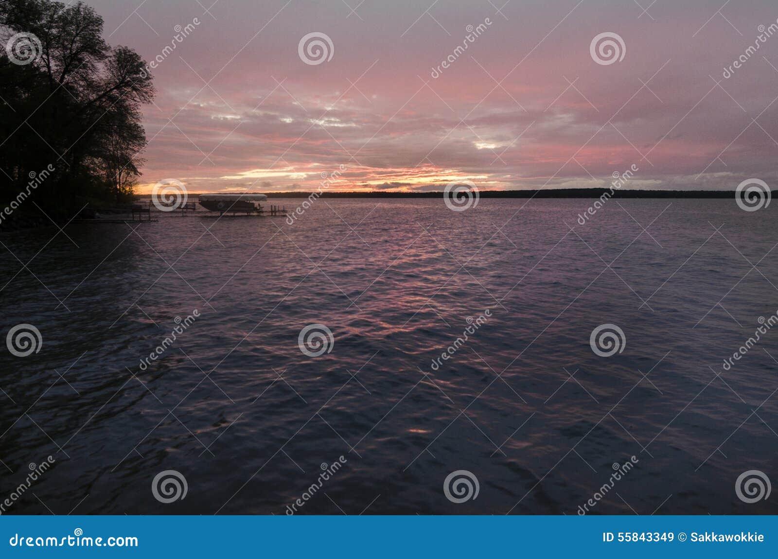 Puesta del sol sobre un lago en Minnesota con el solo barco