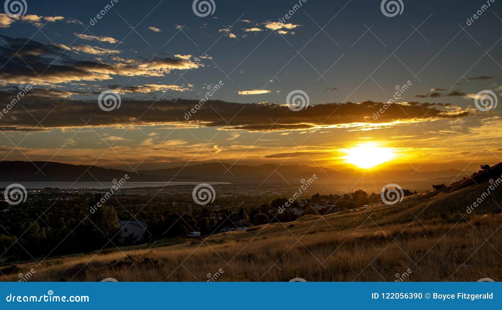 Puesta del sol sobre una ciudad en un valle con las montañas y un lago grande en la distancia