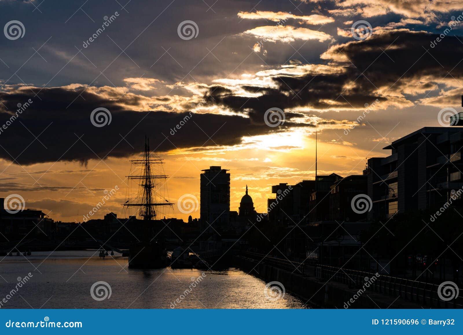 Puesta del sol viva en Dublín, Irlanda que mira sobre el río Liffey con los edificios y Dublin Spire en silueta
