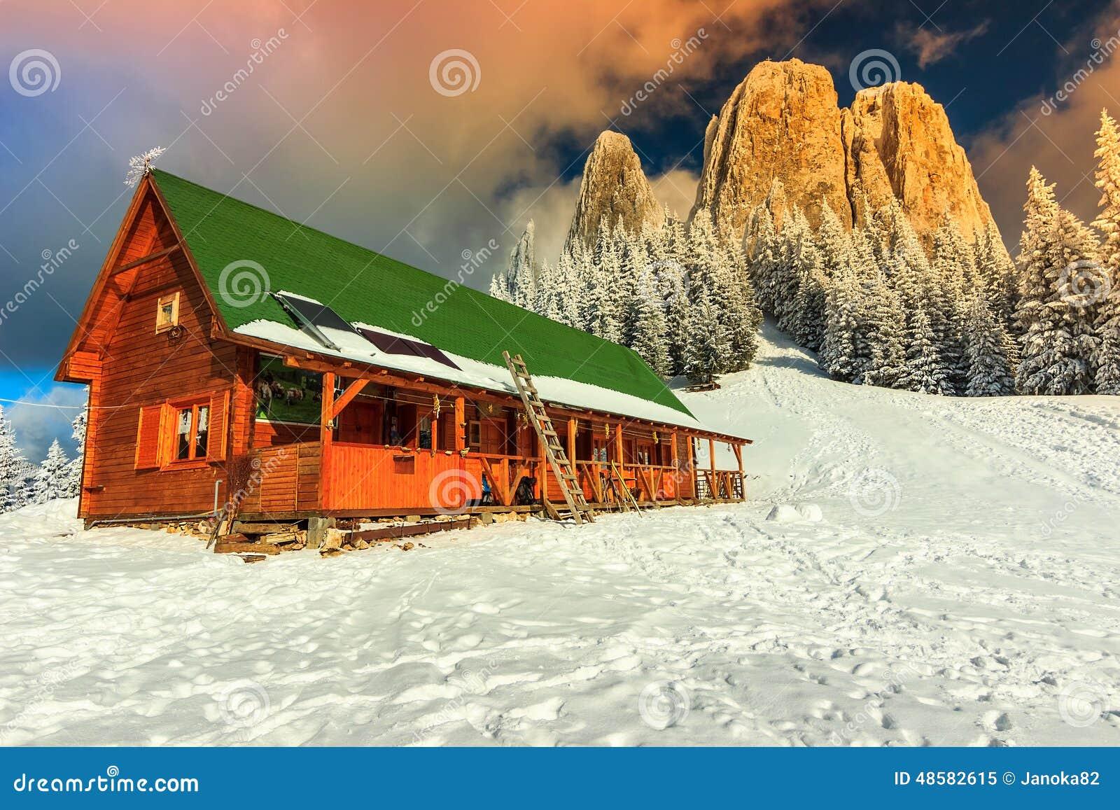Puesta del sol y refugio coloridos, Cárpatos, Transilvania, Rumania, Europa del invierno