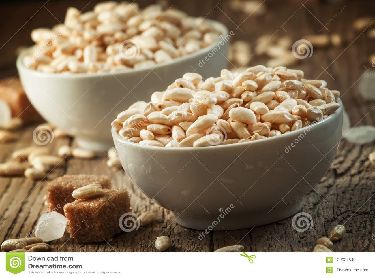 Puffed sweet rice in caramel in white porcelain bowls with cane