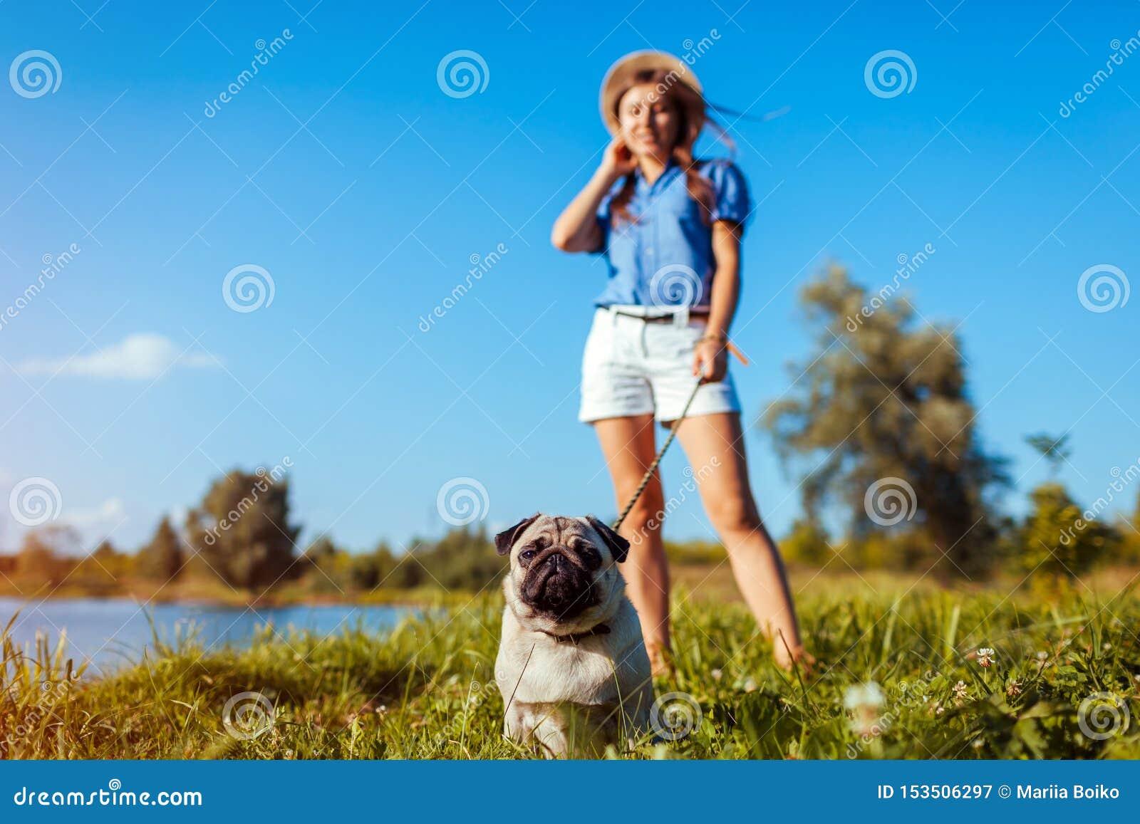 Pughund, der durch Fluss sitzt Gl?cklicher Welpe, der einen Befehl des Meisters wartet Hunde- und der Fraukühlendes Freien