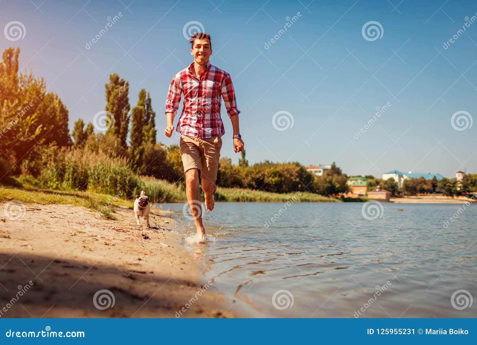 Pughund, der mit Meister durch Fluss spielt Glücklicher Welpe, der Spaß laufen lässt und hat Hunde-pursueing Mann draußen