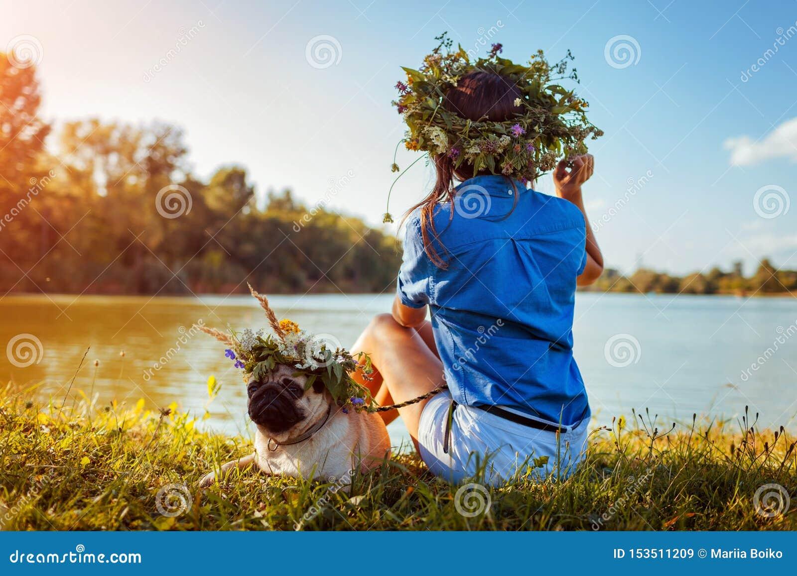 Pughund und sein Meister, die durch tragende Blumenkränze des Flusses kühlen Glücklicher Welpe und Frau, die draußen Sommernatur