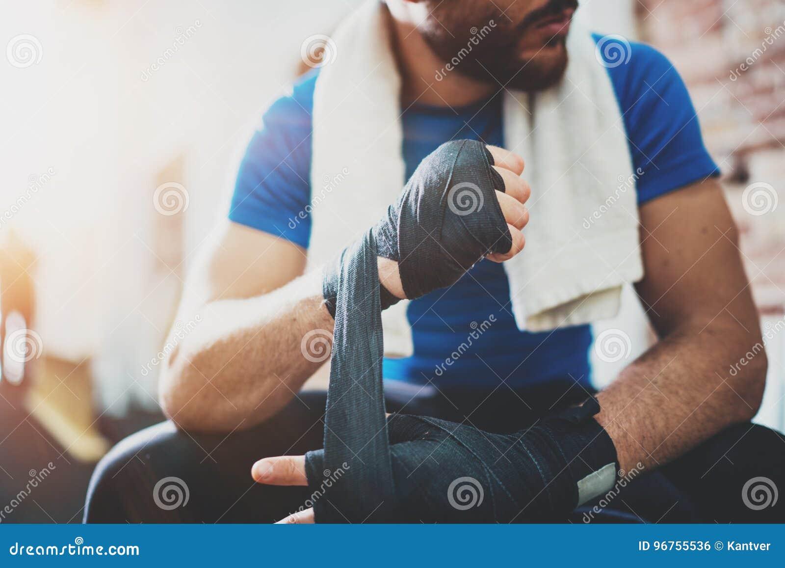 Pugilista novo muscular com as ataduras pretas do encaixotamento Punhos do lutador antes da luta ou do treinamento no gym do espo
