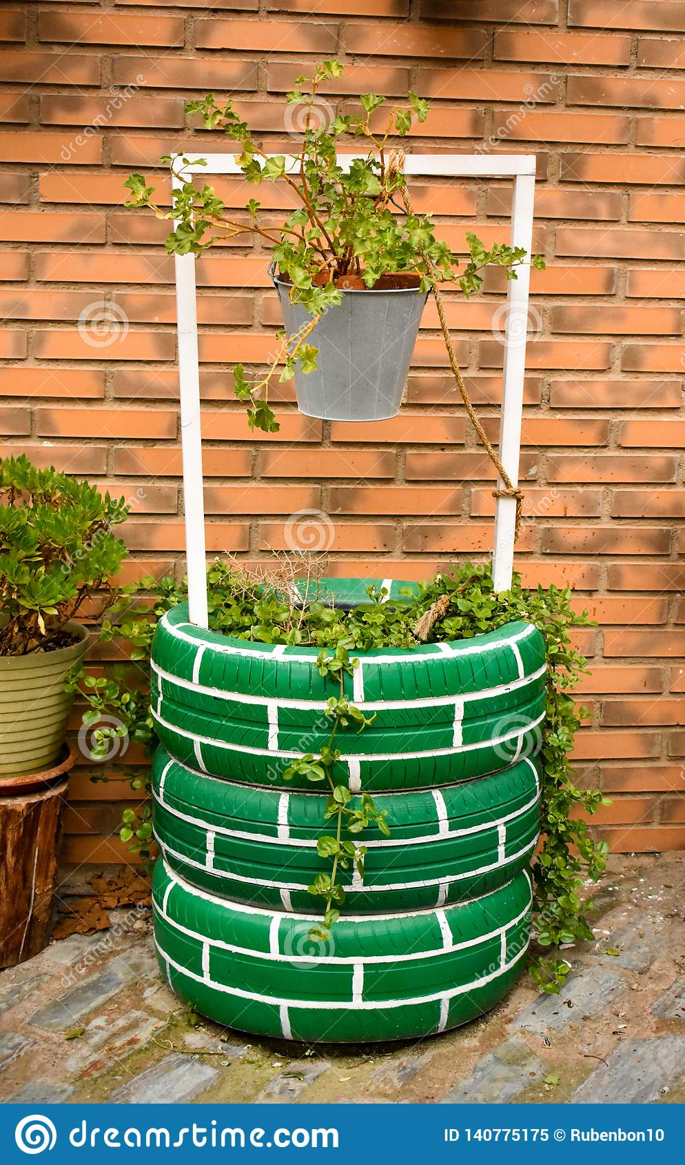 Puits d eau urbain décorant un jardin urbain avec des pneus peints, un seau gris avec des usines sur un fond de brique
